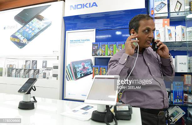 Indiaeconomyconsumersforexeducation by Penelope Macrae Indian vendor Madhusudhan Asawa looks at a display of smart phones at his mobile store in...
