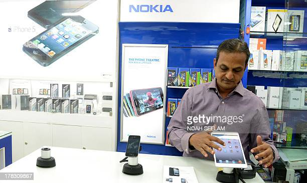 Indiaeconomyconsumersforexeducation by Penelope Macrae Indian vendor Madhusudhan Asawa looks at a display of smart phones and tablets at his mobile...