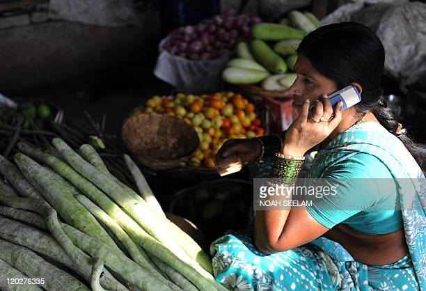 IndiaeconomytelecommobilebankingFOCUS This April 17 2009 shows an Indian vendor using her mobile phone to take customers orders at a wholesale market...