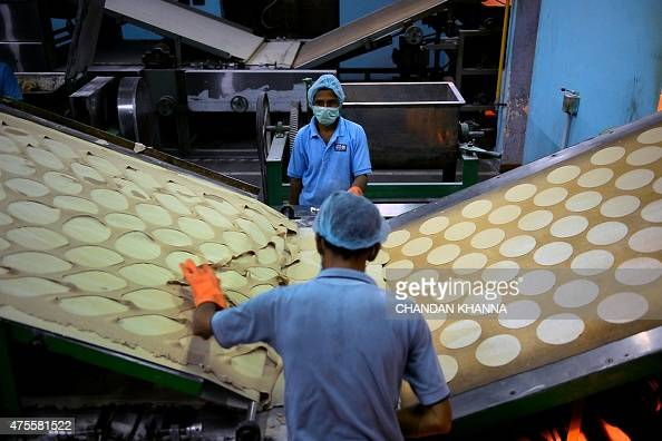 IndiaeducationschoolhealthfoodFEATURE by Abhaya SRIVASTAVA In this photo taken on May 19 Indian labourers work alongisde an automatic 'roti' maker at...