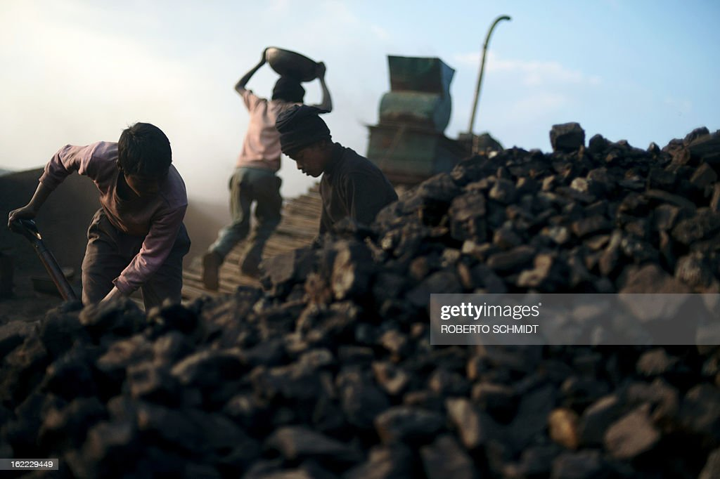 India-mining-children-labour,FEATURE; by Ammu Kannampilly In this photograph taken on January 30, 2013, Indian children carry coal in baskets at a road side coal depot in the East Jaintia Hills district of the Indian northeastern state of Meghalaya. Child labour is officially illegal in India, with several state laws making the employment of anyone under 18 in a hazardous industry a non-bailable offence. Meghalaya, however, has traditionally been exempt due to its special status as a northeastern state with a significant tribal population. According to the Shillong-based non-profit, Impulse NGO Network, some 70,000 children are currently employed in Meghalaya's mines, with several thousand more working at coal depots. AFP PHOTO/ Roberto Schmidt