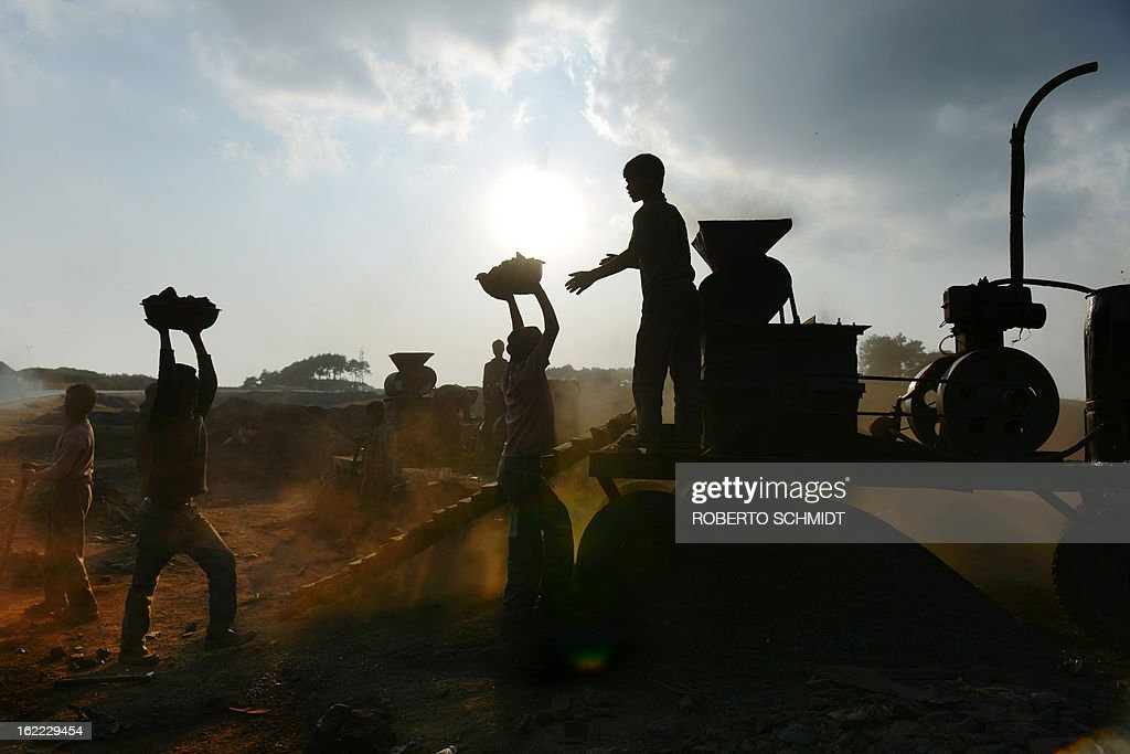 India-mining-children-labour,FEATURE; by Ammu Kannampilly In this photograph taken on January 30, 2013, Indian children carry coal in baskets towards a coal crushing machine at a road side coal depot in the East Jaintia Hills district of the Indian northeastern state of Meghalaya. Child labour is officially illegal in India, with several state laws making the employment of anyone under 18 in a hazardous industry a non-bailable offence. Meghalaya, however, has traditionally been exempt due to its special status as a northeastern state with a significant tribal population. According to the Shillong-based non-profit, Impulse NGO Network, some 70,000 children are currently employed in Meghalaya's mines, with several thousand more working at coal depots. AFP PHOTO/ Roberto Schmidt