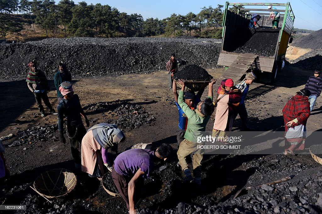India-mining-children-labour,FEATURE; by Ammu Kannampilly In this photograph taken on January 31, 2013, workers shovel coal into baskets at a road side coal depot in Mulang village in the Indian northeastern state of Meghalaya. Child labour is officially illegal in India, with several state laws making the employment of anyone under 18 in a hazardous industry a non-bailable offence. Meghalaya, however, has traditionally been exempt due to its special status as a northeastern state with a significant tribal population. According to the Shillong-based non-profit, Impulse NGO Network, some 70,000 children are currently employed in Meghalaya's mines, with several thousand more working at coal depots. AFP PHOTO/ Roberto Schmidt
