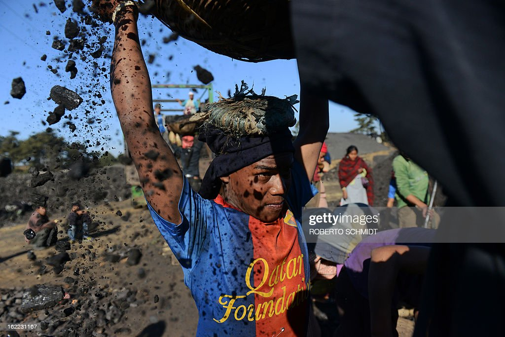 India-mining-children-labour,FEATURE; by Ammu Kannampilly In this photograph taken on January 31, 2013, a young worker places a basket filled with coal on his head at a road side coal depot in the Indian northeastern state of Meghalaya. Child labour is officially illegal in India, with several state laws making the employment of anyone under 18 in a hazardous industry a non-bailable offence. Meghalaya, however, has traditionally been exempt due to its special status as a northeastern state with a significant tribal population. According to the Shillong-based non-profit, Impulse NGO Network, some 70,000 children are currently employed in Meghalaya's mines, with several thousand more working at coal depots. AFP PHOTO/ Roberto SchmidtSchmidt