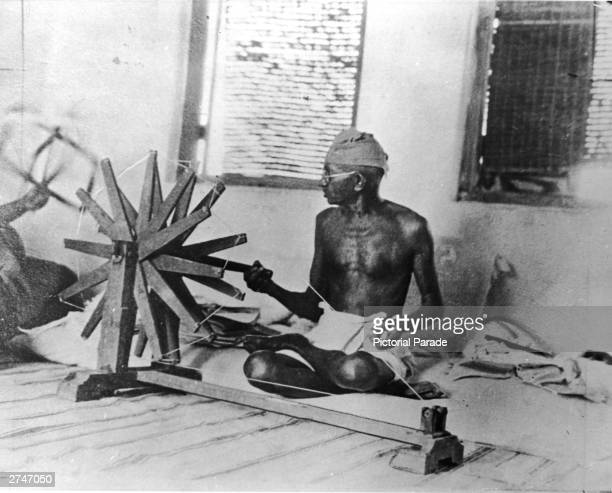 Indian activist Mahatma Gandhi works on a weaving machine circa 1930