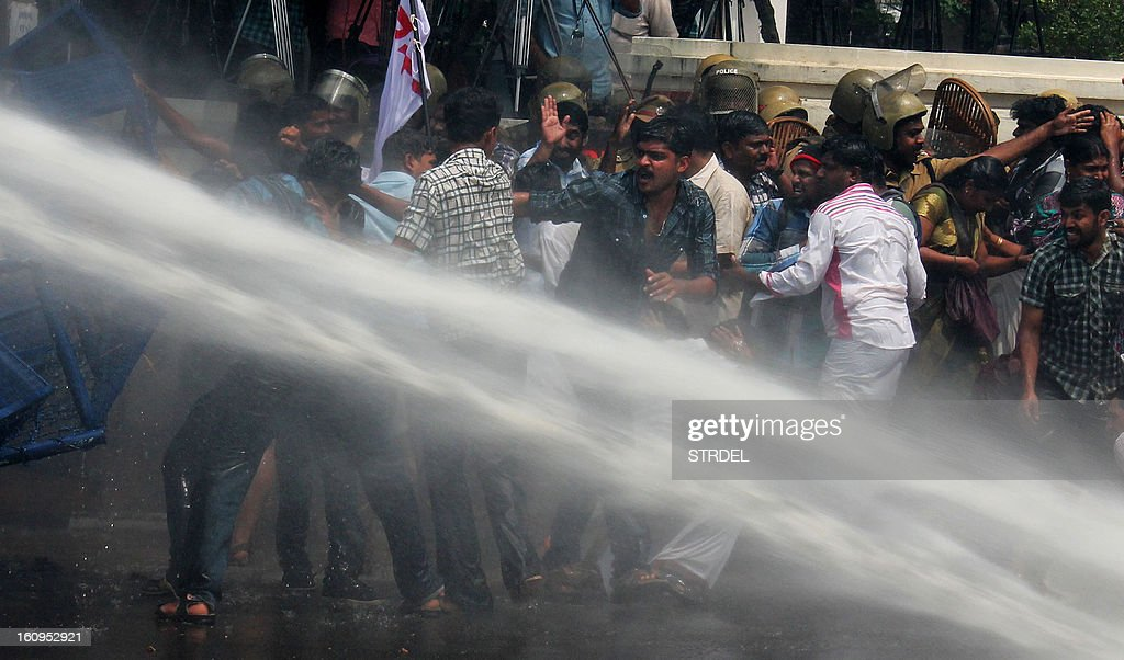 Indian activists clash with police as they are sprayed by a police water cannon during a protest in Thiruvananthapuram on February 8, 2013. Riot police fired water cannons at hundreds of protesters in the Indian state of Kerala demanding the resignation of a lawmaker over allegations he raped a schoolgirl 17 years ago. P.J. Kurien, 72, the deputy speaker of the state's upper house, was acquitted of rape in a trial in 2005 but he has come under new pressure after his accuser demanded a fresh probe in the wake of the storm over a deadly gangrape in Delhi in December. AFP PHOTO/ STR