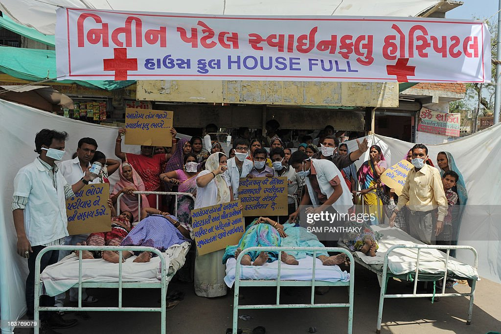 Indian activists dressed as medical staff and patients perform a street play on the ongoing H1N1 swine flu outbreak in Ahmedabad on March 15, 2013. The activists claim that the Gujarat state government has failed to contain the outbreak, with some 110 deaths in the past three months. AFP PHOTO / Sam PANTHAKY