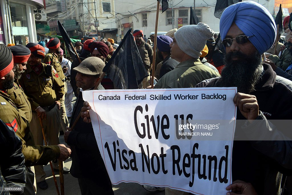 Indian activists from the Canadian Backloggers Pre-2008 Association hold placards as they rally against Canada's Minister of Citizenship, Immigration and Multiculturalism, Jason Kenney during a protest against the delay in processing of their visa applications near the Sikh Shrine Golden temple in Amritsar on January 11,2013. Kenney visited the city to tour the Sikh Shrine and address a press conference where he advised applicants to be cautious of immigration fraud when coming to Canada.