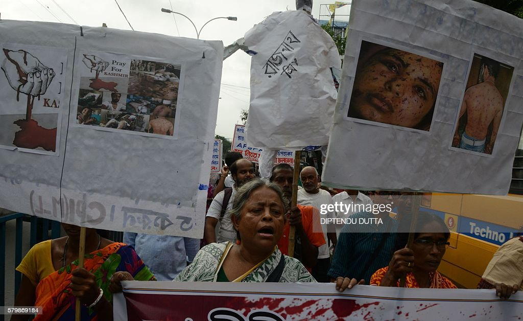 Indian activists from the Communist Party of India hold placards as they shout antigovernment slogans before burning an effigy of Indian Union Home...