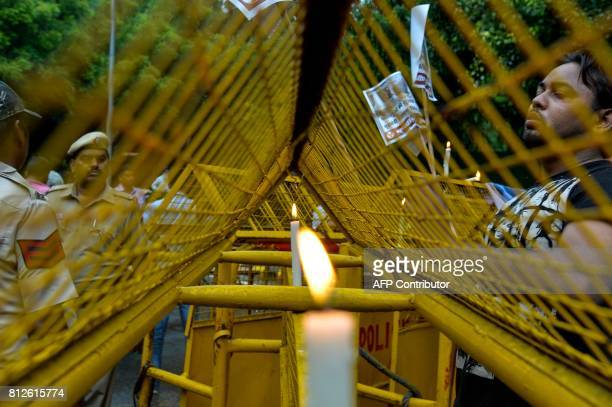 Indian activists from the Indian Youth Congress lights a candle during a protest over an attack on pilgrims taking part in the Amarnath Yatra in New...