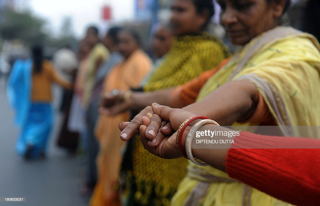 Indian activists from the women's wing of the Communist Party of India- Marxist (CPI-M) takes part in human chain during a protest rally in Siliguri on February 4,2013. Over four thousand women took part in a general protest rally demanding the safety of women and also against price hike of essential commodities. AFP PHOTO/ Diptendu DUTTA