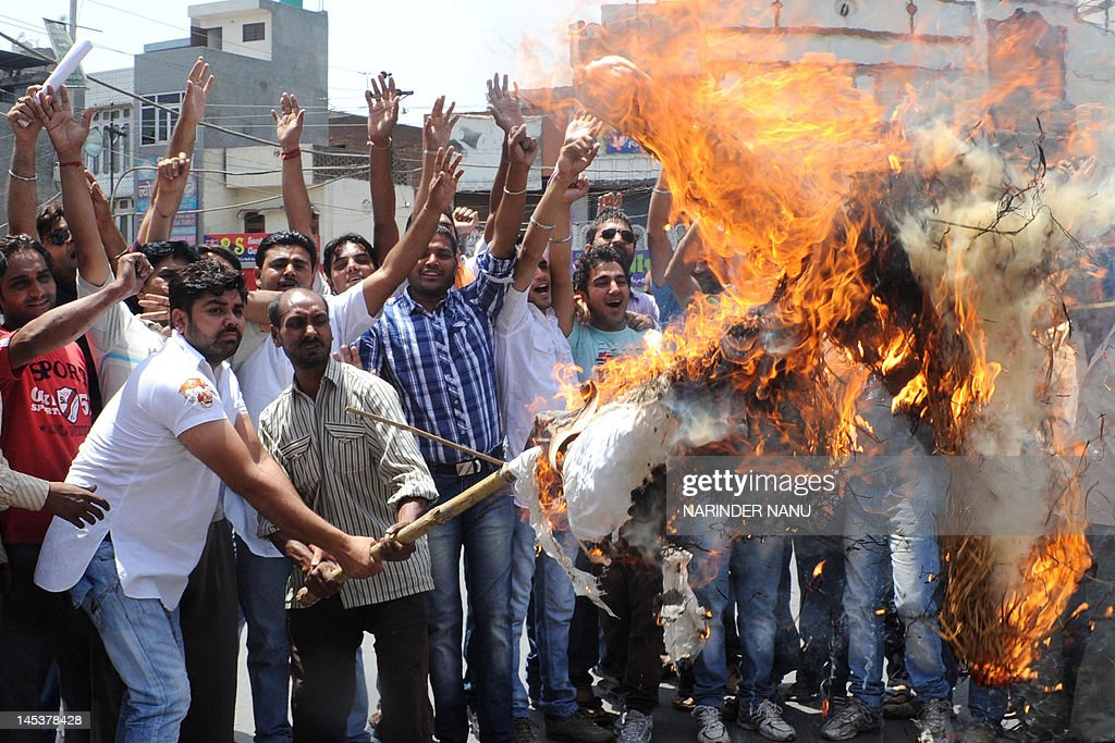 Indian activists from the Yuva Shere Punjab welfare association shout anti-government slogans as they burn an effigy of Indian Cabinet Minister for Petroleum and Natural Gas, Jaipal Reddy, during a protest against the petrol price hike in Amritsar on May 28, 2012. Indian state-run oil firms announced the sharpest hike in petrol prices in nearly a decade to offset growing losses caused by subsidised rates, rises in the international oil price and a plunging rupee. The increase was put at 6.28 rupees (11 US cents) per litre which, when taxes are included, will mean a 7.5-rupee hike for consumers in India from May 24.