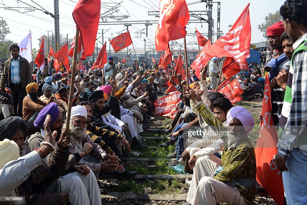 Indian activists from various trade unions block the tracks during a two-day strike opposing the current UPA government's economic policies at the railway station in Amritsar on February 20, 2013. Millions of India's workers walked off their jobs in a two-day nationwide strike called by trade unions to protest at the 'anti-labour' policies of the embattled government. Financial services and transport were hit by the strike called by 11 major workers' groups to protest at a series of pro-market economic reforms announced by the government last year, as well as high inflation and rising fuel prices. AFP PHOTO/ NARINDER NANU