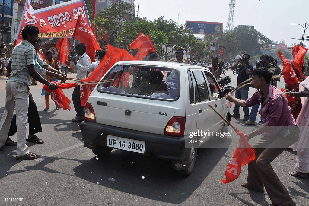 Indian activists from various trade unions smash windows to a car during a two-day strike opposing the current UPA government's economic policies in Bhubaneswar on February 20, 2013. Millions of India's workers walked off their jobs on Wednesday in a two-day nationwide strike called by trade unions to protest at the 'anti-labour' policies of the embattled government.