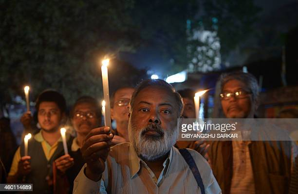 Indian activists hold candles as they participate in a mass meeting to protest against the gangrape and murder of a teenager in Kolkata on January 2...