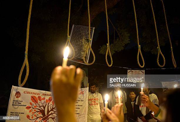 Indian activists hold candles near hangman's nooses during a candle light march to mark the second anniversary of the fatal gangrape of a student in...