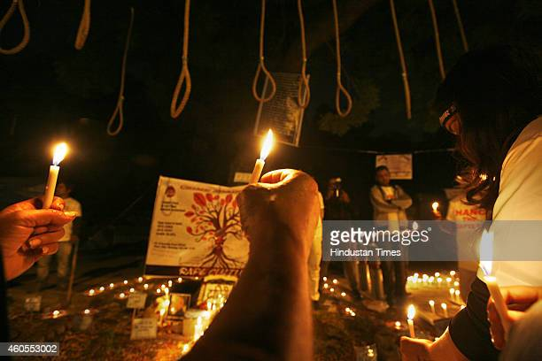 Indian activists hold candles near hangman's nooses during a candle light march to mark the second anniversary of the fatal gangrape of a student on...