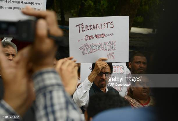 Indian activists hold placards as they shout slogans during a protest to condemn an attack on pilgrims taking part in the annual Amarnath Yatra in...