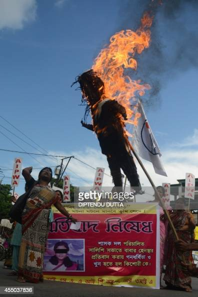 Indian activists of All India Progressive Women Association shout slogans as they burn an effigy of West Bengal Chief Minister Mamata Banerjee during...