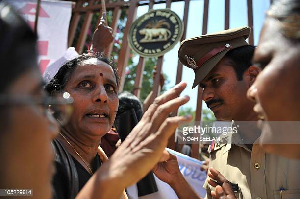 Indian activists of The AllIndia Democratic Women's Association face police as they protest in front of the Reserve Bank of India against Micro...