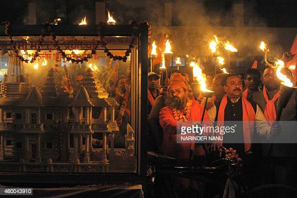 Indian activists of the Hindu Bajrang Dal Party hold torches near a model of the Ram Temple during a procession marking the 22nd anniversary of the...