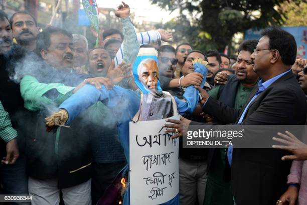 TOPSHOT Indian activists of the Trinamool Congress shout slogans as they burn an effigy of Prime Minister Narendra Modi during a protest meeting in...