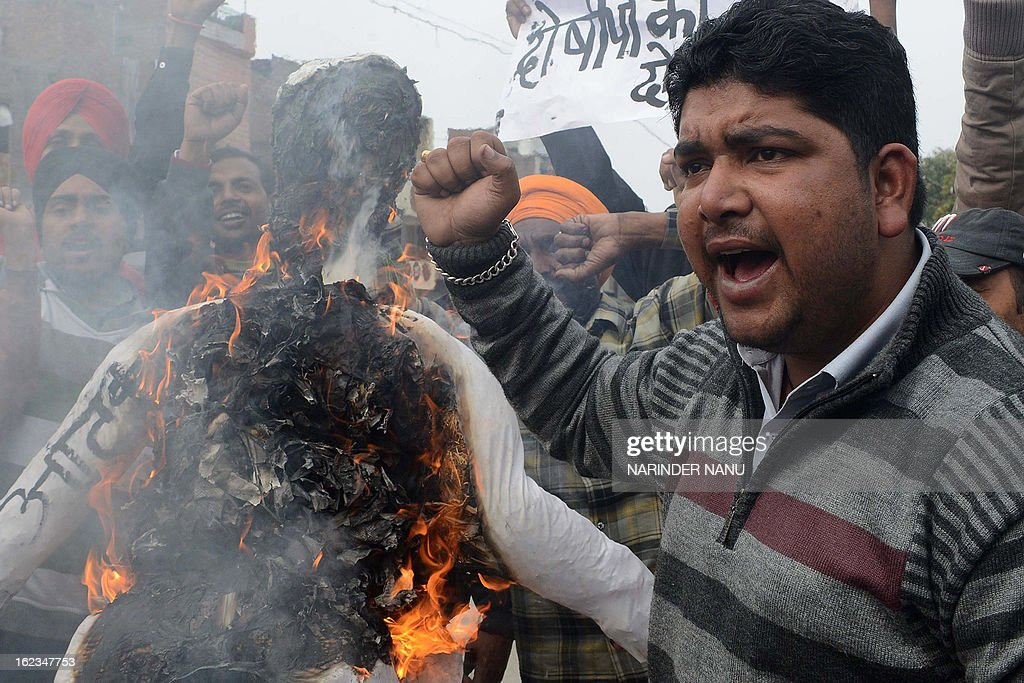 Indian activists of Youth Bhagwan Valmiki Mahasangh Punjab burn an effigy of a terrorist and shout slogans condemning the twin bomb blasts in Hyderabad during a demonstration in Amritsar on February 22, 2013. Indian police revealed Friday they had been warned of a possible attack by Islamist militants in a bustling shopping area of Hyderabad where twin bombings killed at least 14 people and wounded scores. AFP PHOTO/NARINDER NANU