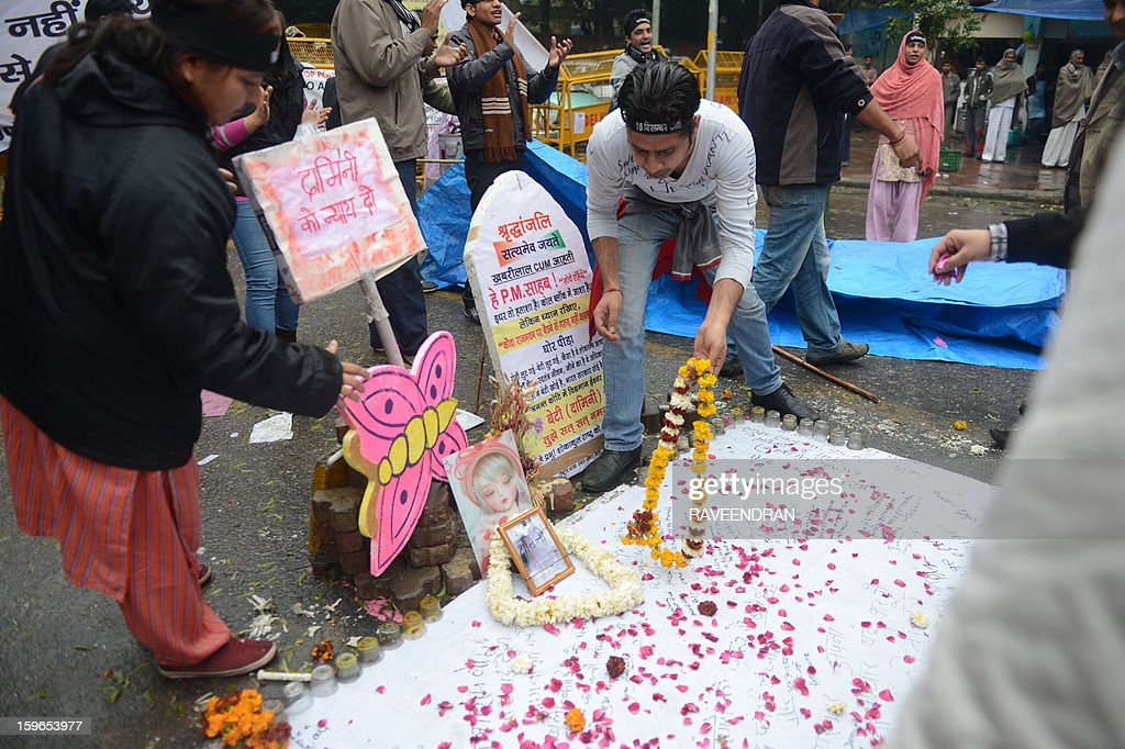 Indian activists pray at a memorial to rape victims during a protest against the gang rape and murder of a student in New Delhi on January 18, 2013. After one month of lurid reporting on a horrifying gang-rape and murder of a student in New Delhi, women in the Indian capital say they are not safe in the Indian capital and prosecutors said that the five adults charged are 'dangerous men' and should be handcuffed while in custody.