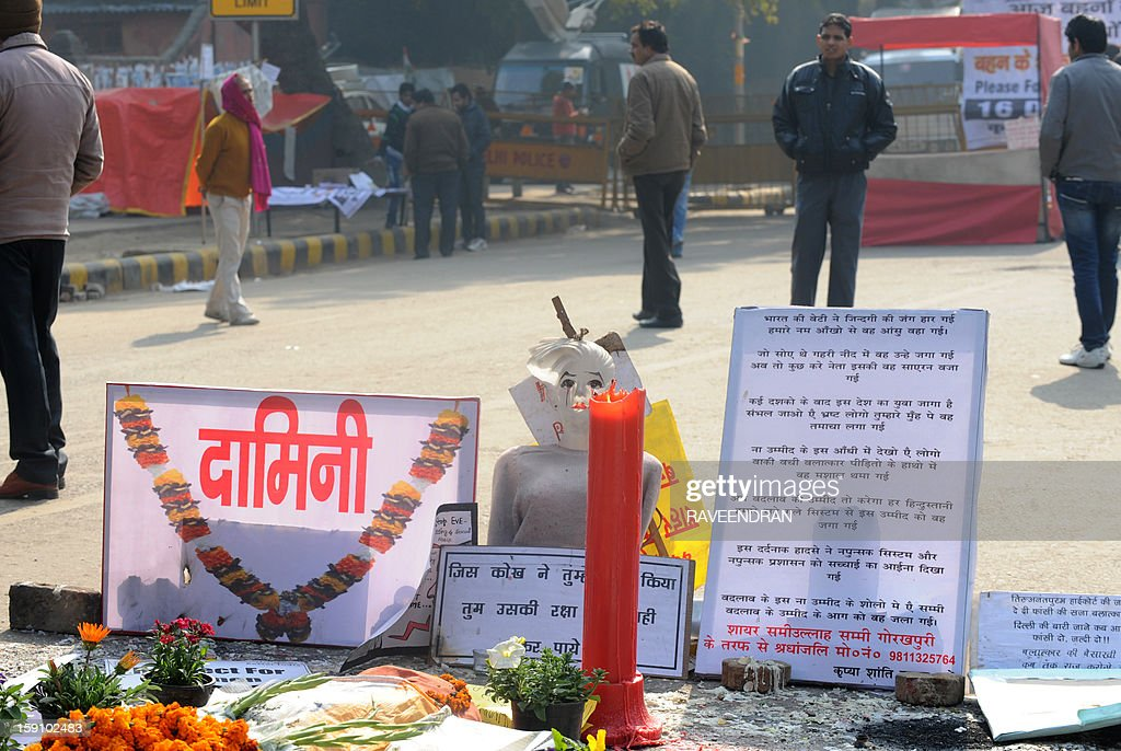 Indian activists stand near a memorial to a rape victim during a protest in New Delhi on January 8, 2013, against the gang rape and murder of a student. Five men appeared in court for the first time on January 7,to face charges over the murder and gang-rape of a 23-year-old student in New Delhi amid chaotic scenes that forced the hearing behind closed doors. AFP PHOTO/ RAVEENDRAN