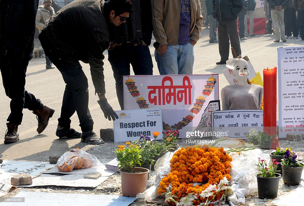 Indian activists stand near a memorial to a rape victim during a protest in New Delhi on January 8, 2013, against the gang rape and murder of a student. Five men appeared in court for the first time on January 7,to face charges over the murder and gang-rape of a 23-year-old student in New Delhi amid chaotic scenes that forced the hearing behind closed doors.