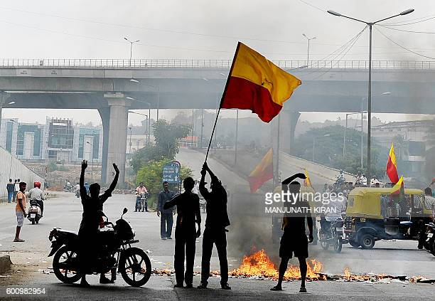 Indian activists wave the Karnataka flag as they block traffic on a major connecting road during a statewide strike in Bangalore on September 9 2016...