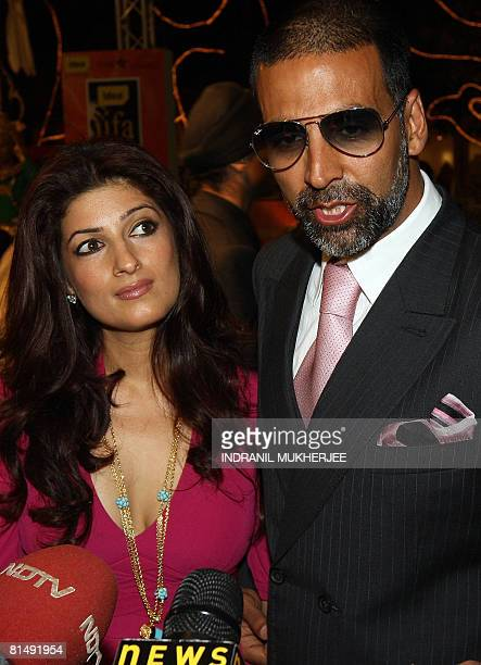 Indian actor Akshay Kumar speaks to the media as wife Twinkle Khanna watches on after they arrived for the International Indian Film Academy Awards...