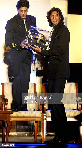 Indian actor and coowner of the 'Kolkata' cricket team Shahrukh Khan hands over a replica helmet to Pace bowler Ishant Sharma during a press meet in...