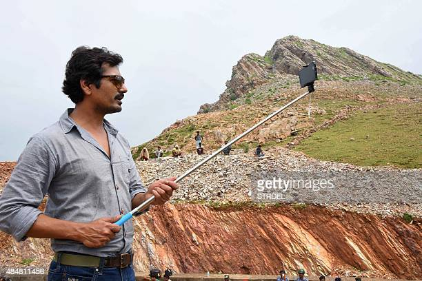 Indian actor Nawajuddin Siddique uses a 'selfie' stick as he poses for a photograph during a promotional event for the forthcoming fil 'Manjhi the...