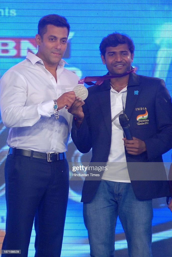 Indian actor Salman Khan giving away the special achievement award to London Paralympics silver medalist Girisha H Nagarajegowda during IBN 7 Super Idol awards 2012 ceremony at Taj Lands end, Bandra on November 25, 2012 in Mumbai, India.