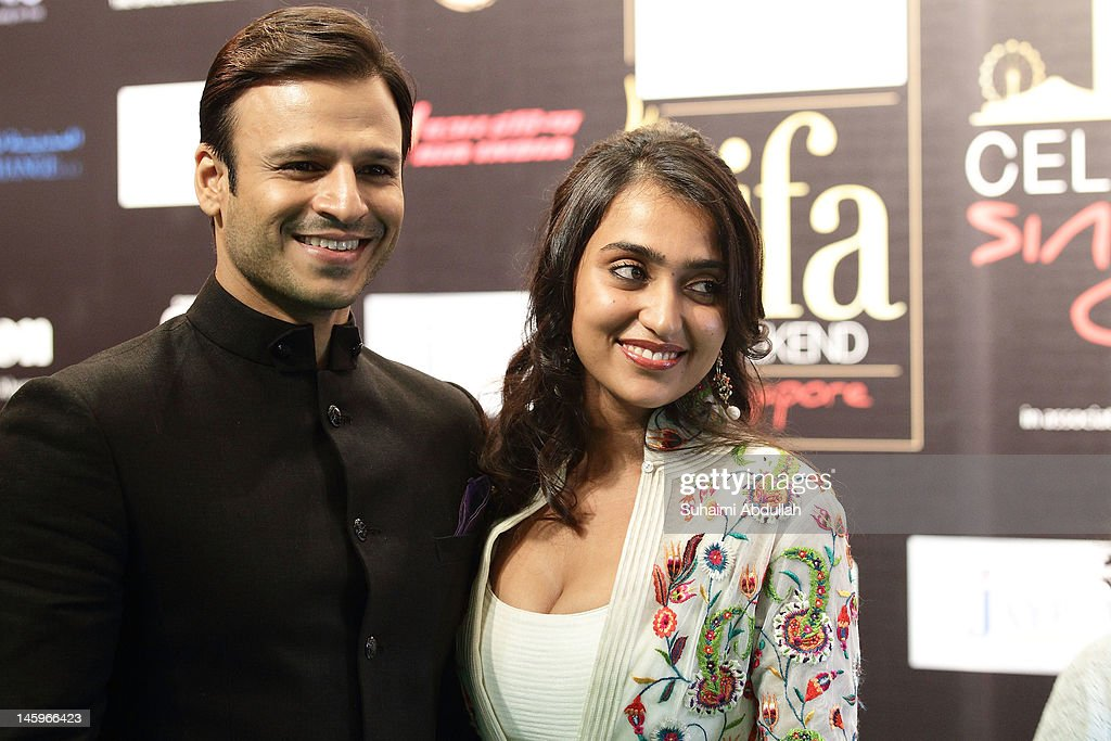 Indian actor <a gi-track='captionPersonalityLinkClicked' href=/galleries/search?phrase=Vivek+Oberoi&family=editorial&specificpeople=627274 ng-click='$event.stopPropagation()'>Vivek Oberoi</a> (L) and wife pose on the green carpet during the IIFA Rocks Green Carpet on day two of the 2012 International India Film Academy Award weekend at the Esplanade on June 8, 2012 in Singapore.