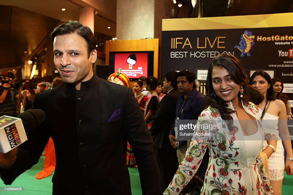 Indian actor <a gi-track='captionPersonalityLinkClicked' href=/galleries/search?phrase=Vivek+Oberoi&family=editorial&specificpeople=627274 ng-click='$event.stopPropagation()'>Vivek Oberoi</a> (L) speaks to the media accompanied by his wife on the green carpet during the IIFA Rocks Green Carpet on day two of the 2012 International India Film Academy Award weekend at the Esplanade on June 8, 2012 in Singapore.