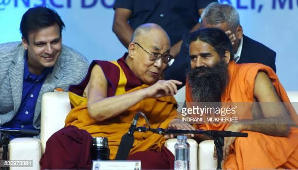 Indian actor Vivek Oberoi strains to listen as Tibetan spiritual leader The Dalai Lama speaks with Indian Yoga Guru Baba Ramdev during a inter faith...