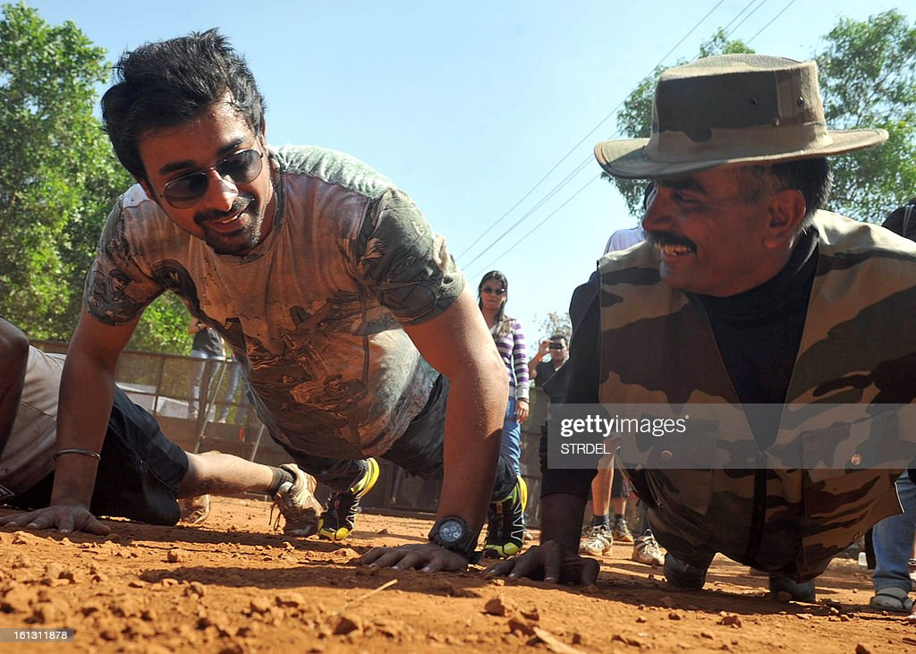 Indian actor VJ Rannvijay Singh Singha (L) performs push ups during the Mud Rush event in Kolad, India's Maharashtra state, on February 9, 2013.