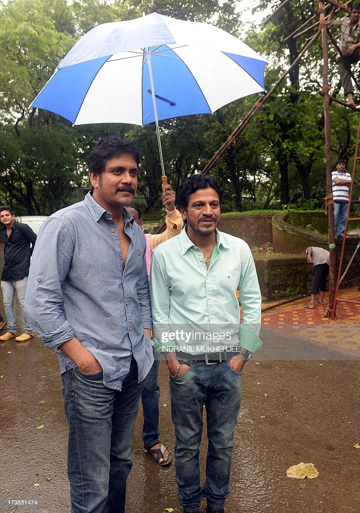 Indian actors Nagarjun (L) and Shivraj Kumar stand in the rain as they wait to shoot a television commercial for a leading jewellery house in Mumbai on July 16, 2013. Indian filmstars who enjoy demigod status among their fans are the most sought after by entrepreneurs for endorsing brands from shampoo to shoe lace.