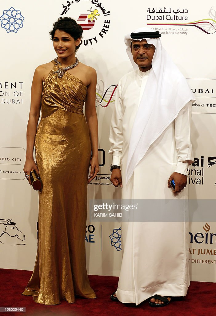 Indian actress Freida Pinto (L) poses for a photo with the Chairman of the Dubai International Film Festival Abdulhamid Juma during the opening ceremony in the Gulf emirate of Dubai on December 9, 2012. AFP PHOTO/KARIM SAHIB