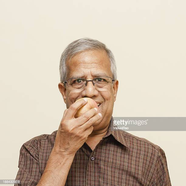 Indian adult man eating apple