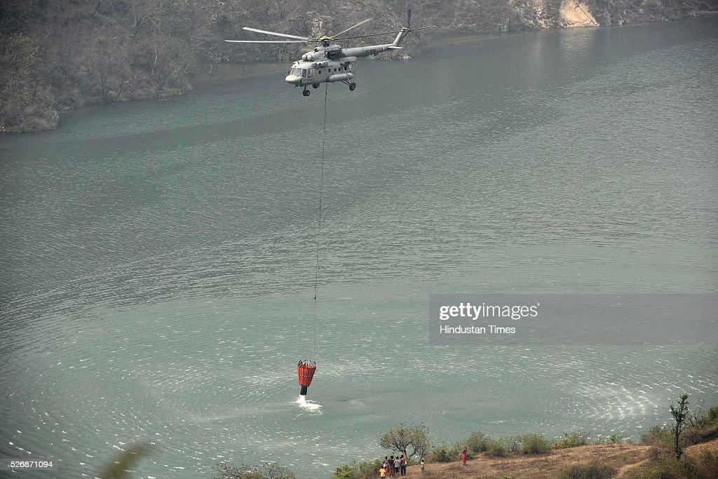 Indian Air Force deployed 11-members team with Mi-17 helicopter begin fire fighting operations to control the fire, on May 1, 2016 in Uttarakhand, India. Two Indian Air Force (IAF) choppers began spraying water over the burning forests in Uttarakhand on Sunday morning. Major forest fires raged across Uttarakhand even as two Indian Air Force (IAF) choppers have begun spraying water to extinguish the flames. Presently, some 5,000 workers -- including 3,000 daily wagers -- are engaged in putting out the fire. More than 2300 hectares of forest have been gutted in the fire since it was first reported in February this year. Dry winters and soaring temperatures are blamed for the fire that has affected all 13 districts of the state.