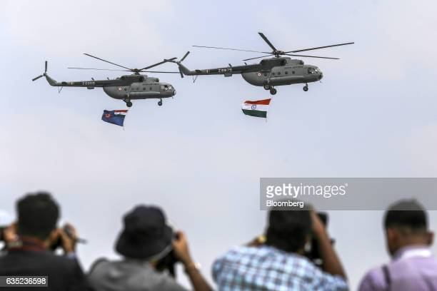 Indian Air Force Mil Mi17 helicopters carry an Indian national flag during a flypast at the opening ceremony of the Aero India air show at Air Force...