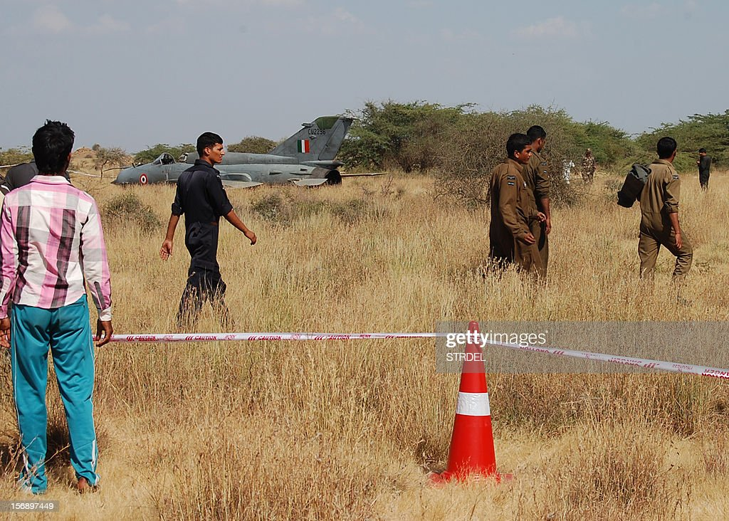 Indian Air Force (IAF) personnel walk through the site where a MiG-21'Bison' aircraft crashed after taking off from Naliya Airbase in Gujarat on November 24, 2012. The pilot of the aircraft ejected safely, sources said, adding that it was on a routine training sortie. AFP PHOTO / STR