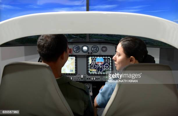 Indian Air Force pilots sit in a flight simulator at an aviation stall in the exhibition area on the ithird day of the 11th edition of 'Aero India' a...
