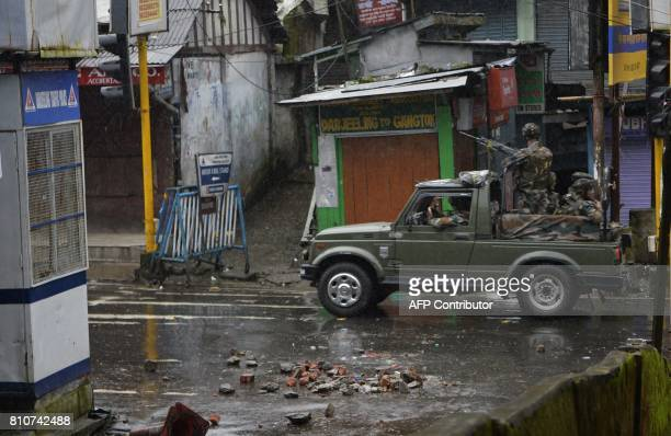Indian amry personeel patrol atop a vehicle along a streets following clashes following clashes with Gorkhaland supporters during an indefinite...
