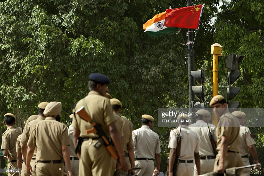 Indian and Chinese flags affixed to a lamp post flutter in the wind as Indian police personnel head to their positions in New Delhi on May 20, 2013, following a briefing as they provide security during the visit of Chinese Premier Li Keqiang. Visiting Chinese Premier Li Keqiang is scheduled to hold talks with a string of Indian leaders as the two sides look to rebuild trust after a recent flare-up in a border dispute as well as boost trade. AFP PHOTO/TENGKU BAHAR