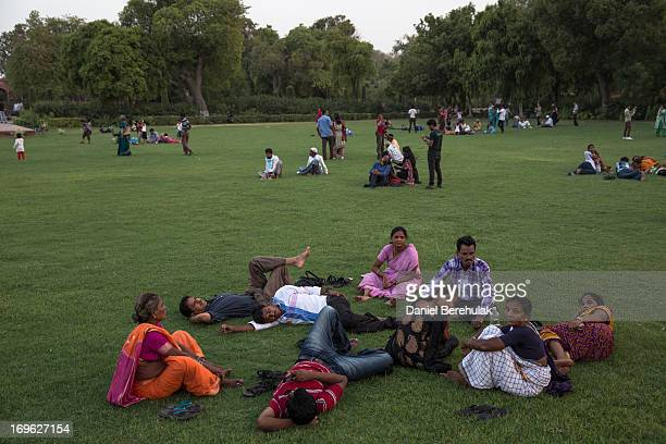 Indian and foreign tourists sit on the lawn as they visit the Taj Mahal on May 29 2013 in Agra India Completed in 1643 the mausoleum was built by the...