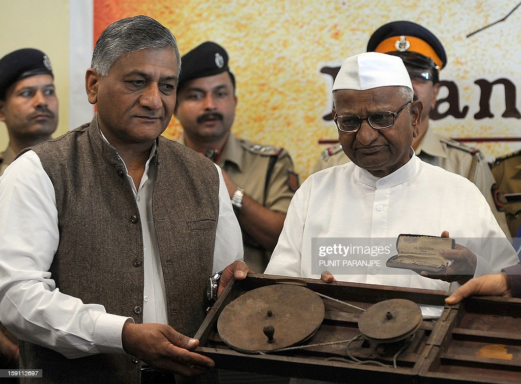 Indian anti-corruption activist Anna Hazare (R) and retired Indian Army General V.K.Singh (2L) hold some of the personal memorabilia of Mahatma Gandhi during a news conference at the international airport terminal in Mumbai on January 8, 2013. Gandhi's pair of iconic spectacles, a famous wooden 'charkha' which he personally used, a signed prayer book, several letters and other documents pertaining to Gandhi's life, and 24 other personal memorabilia were auctioned in London on April 17, 2012 and purchased by Indian industrialist Kamal Morarka who handed over the memorabilia to Hazare and his team. The memorabilia will be showcased in a tour around the country.
